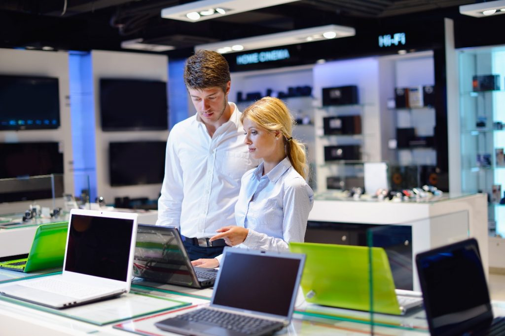 man looking at laptop with saleswoman
