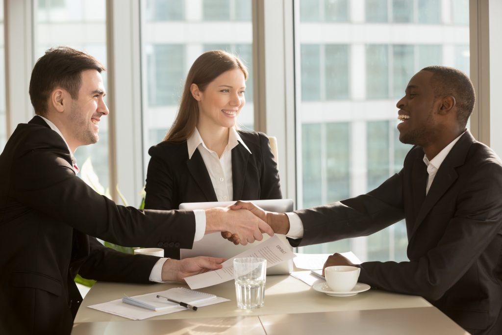 two man shaking hands over a contract with a woman also seated at the table